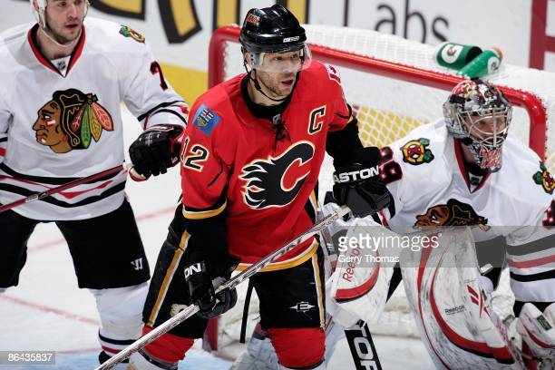 Jarome Iginla of the Calgary Flames skates against Nikolai Khabibulin and Brent Seabrook of the Chicago Blackhawks during Game Six of the Western...