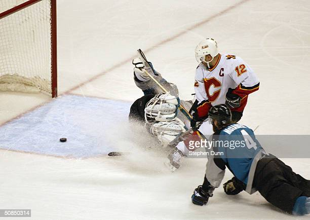 Jarome Iginla of the Calgary Flames slides the puck past goaltender Evgeni Nabokov and Kyle McLaren of the San Jose Sharks into the goal in Game five...