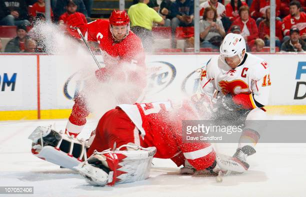 Jarome Iginla of the Calgary Flames snows Jimmy Howard of the Detroit Red Wings as Nicklas Lidstrom of the Detroit Red Wings looks on during their...