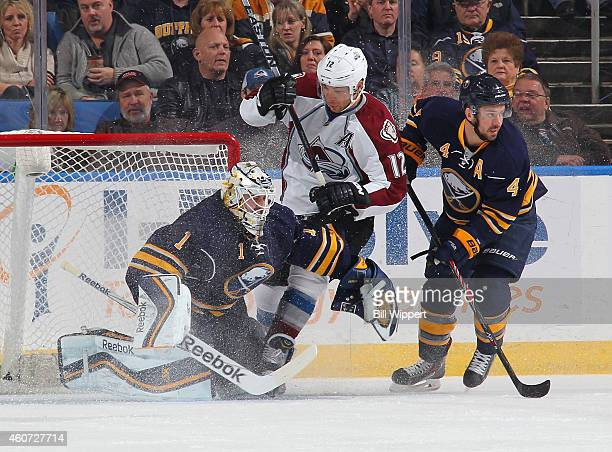 Jarome Iginla of the Colorado Avalanche crashes the net defended by Jhonas Enroth and Josh Gorges of the Buffalo Sabres on December 20 2014 at the...