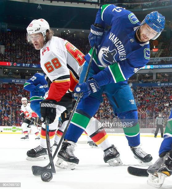 Jaromir Jagr of the Calgary Flames and Alexander Burmistrov of the Vancouver Canucks battle for the puck during their NHL game at Rogers Arena...