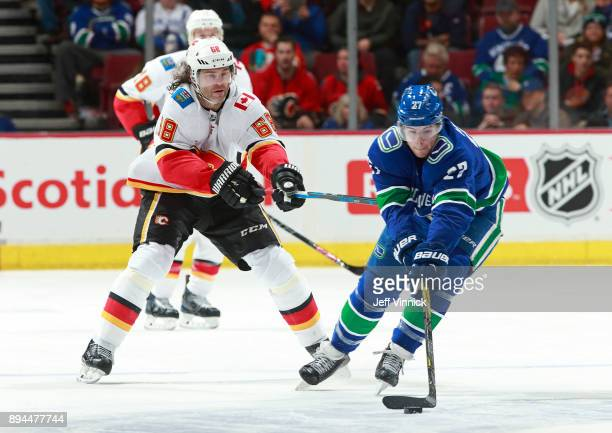 Jaromir Jagr of the Calgary Flames checks Ben Hutton of the Vancouver Canucks during their NHL game at Rogers Arena December 17 2017 in Vancouver...