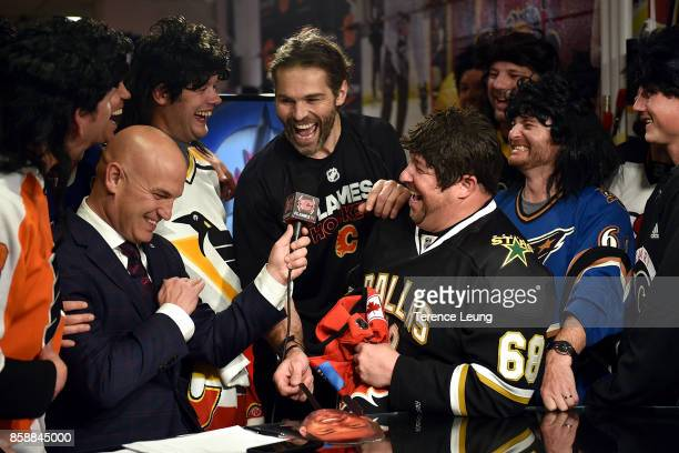 Jaromir Jagr of the Calgary Flames is interviewed with the Travelling Jagrs during an intermission during an NHL game against the Winnipeg Jets on...