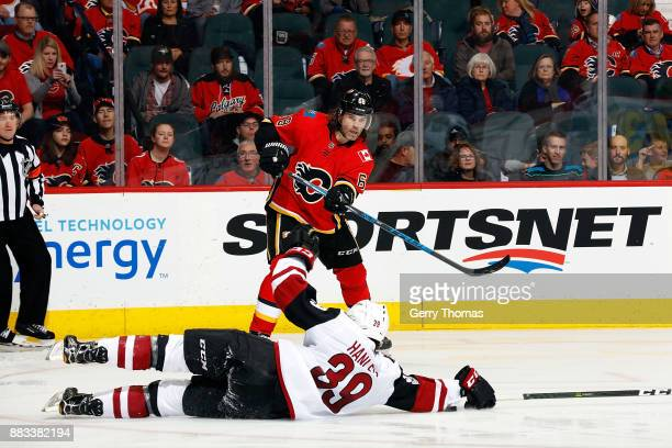 Jaromir Jagr of the Calgary Flames passes the puck through Joel Hanley of the Arizona Coyotes during an NHL game on November 30 2017 at the...