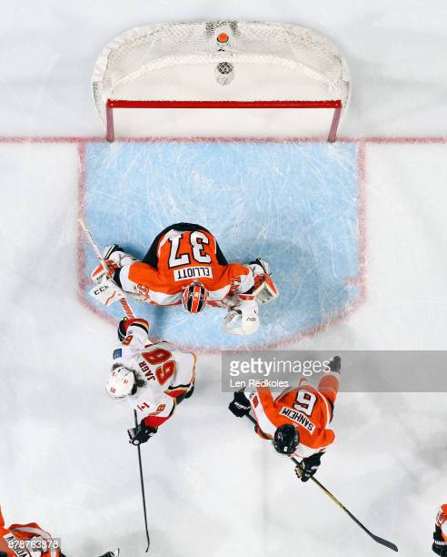 Jaromir Jagr of the Calgary Flames waits atop the crease to deflect a shot on goal against Travis Sanheim and Brian Elliott of the Philadelphia...