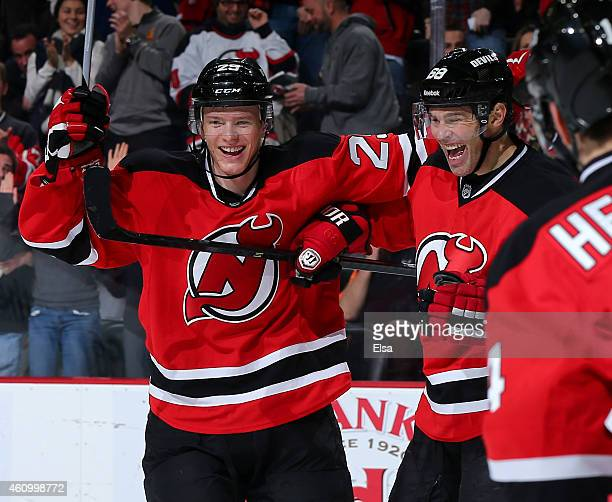 Jaromir Jagr of the New Jersey Devils celebrates his hat trick with teammate Seth Helgeson after Jagr scored in the second period against the...
