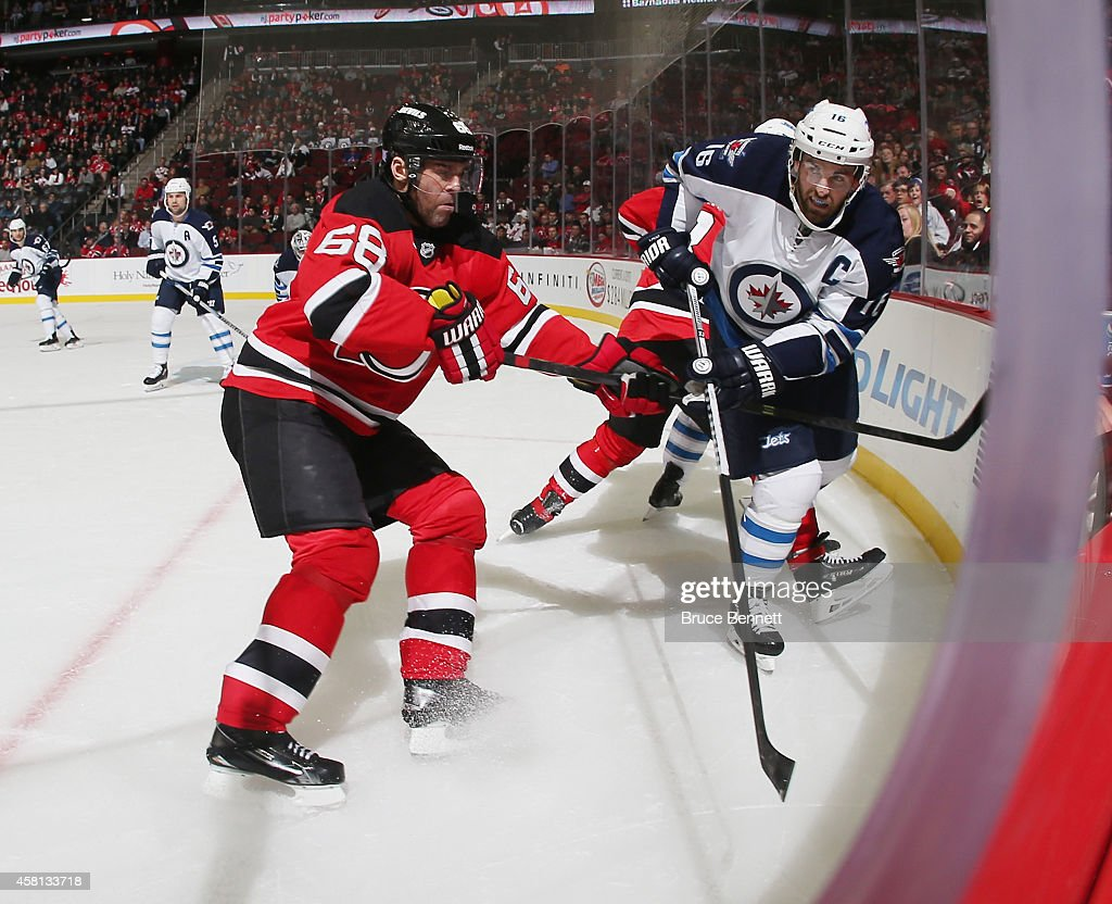 Jaromir Jagr #68 of the New Jersey Devils checks Andrew Ladd #16 of the Winnipeg Jets at the Prudential Center on October 30, 2014 in Newark, New Jersey. The Devils defeated the Jets 2-1 in the shootout.