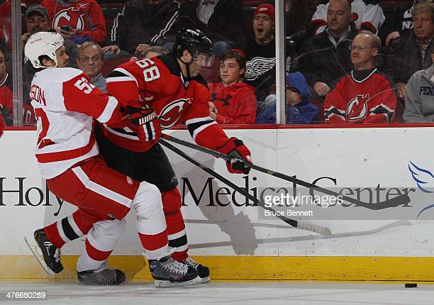 Jaromir Jagr of the New Jersey Devils is held back by Jonathan Ericsson of the Detroit Red Wings during the second period at the Prudential Center on...