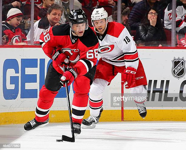 Jaromir Jagr of the New Jersey Devils takes the puck as Jay McClement of the Carolina Hurricanes defends on February 21 2015 at the Prudential Center...