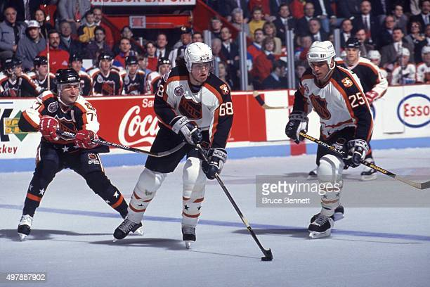 Jaromir Jagr of the Wales Conference and the Pittsburgh Penguins skates with the puck as Paul Coffey of the Campbell Conference and the Los Angeles...