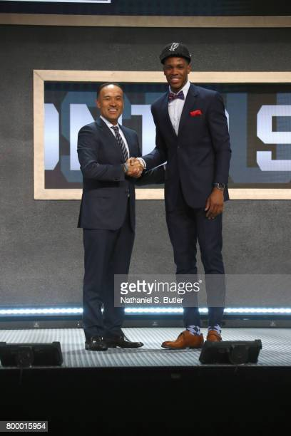 Jaron Blossomgame shakes hands with Deputy Commissioner Mark Tatum after being selected number fifty ninth overall by the San Antonio Spurs during...