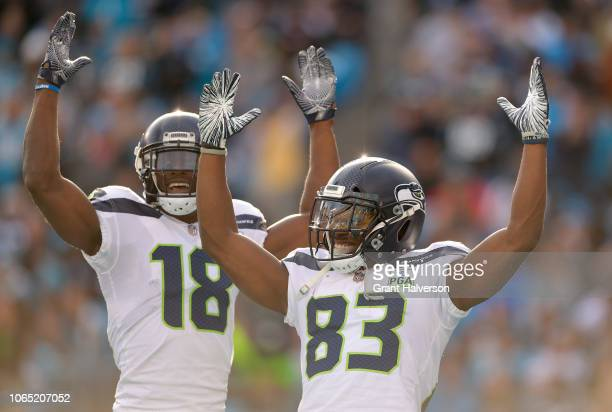 Jaron Brown celebrates with teammate David Moore of the Seattle Seahawks after a touchdown against the Carolina Panthers in the fourth quarter during...