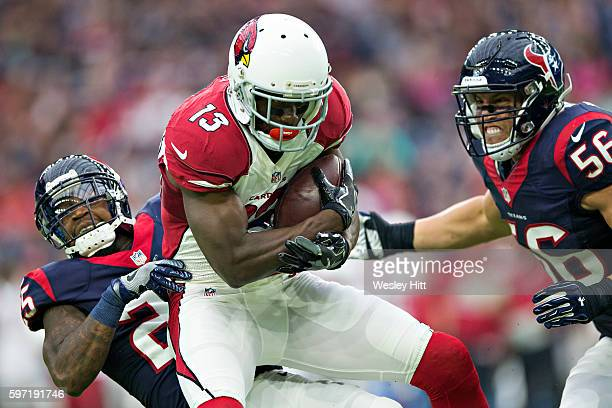 Jaron Brown of the Arizona Cardinals catches a pass during a preseason game and is tackled by Kareen Jackson and Brian Cushing of the Houston Texans...