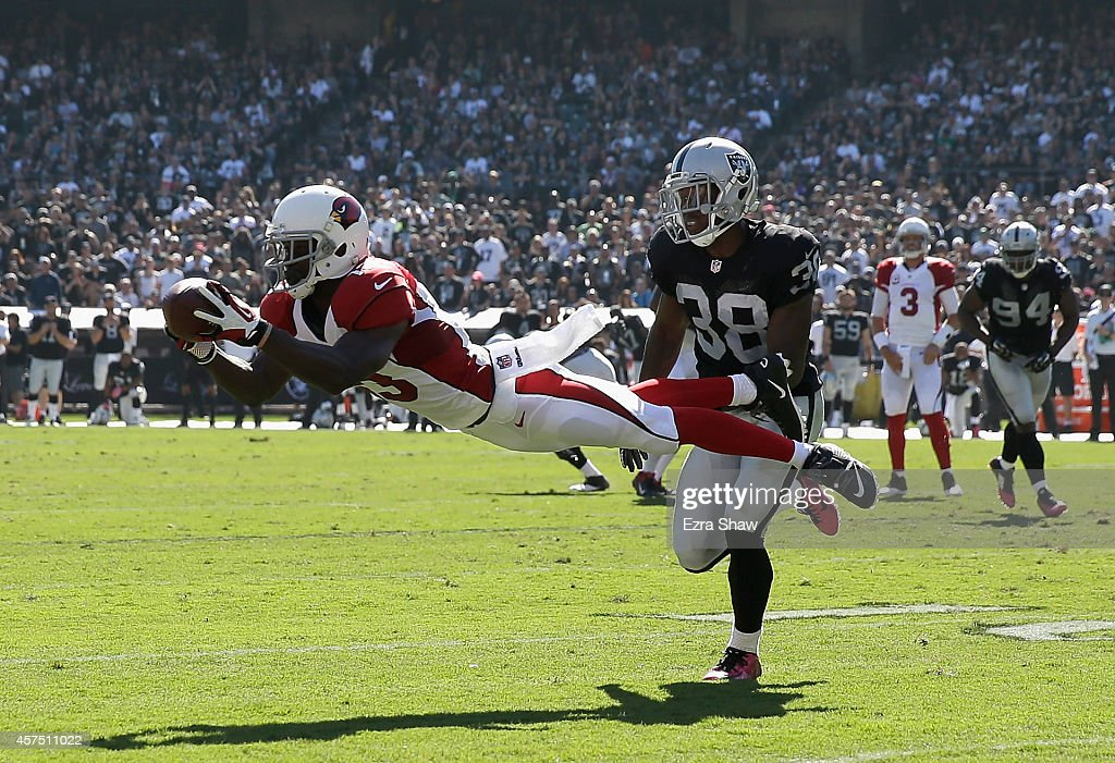 Jaron Brown #13 of the Arizona Cardinals makes the diving catch in front of T.J. Carrie #38 of the Oakland Raiders in the first half at O.co Coliseum on October 19, 2014 in Oakland, California.