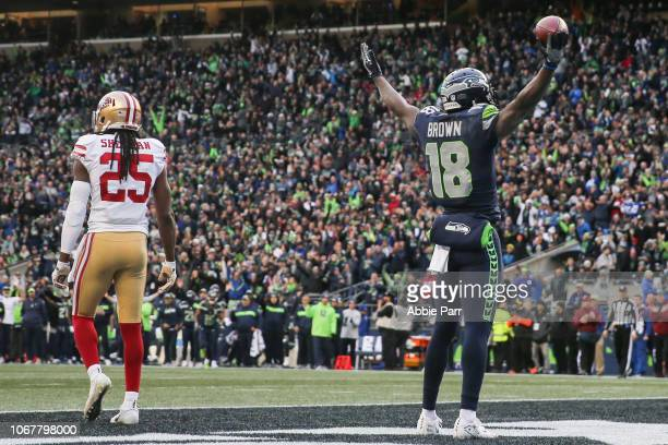 Jaron Brown of the Seattle Seahawks celebrates a touchdown in the third quarter as Richard Sherman of the San Francisco 49ers walks away at...