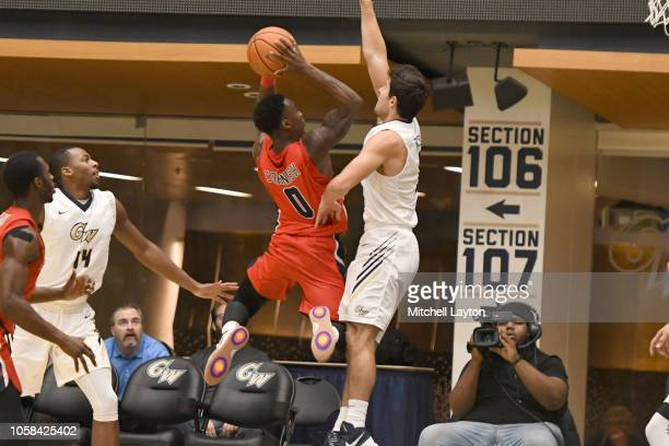 Jaron Cornish of the Stony Brook Seawolves drives to the basket over Adam Mitola of the George Washington Colonials during a college basketball game...