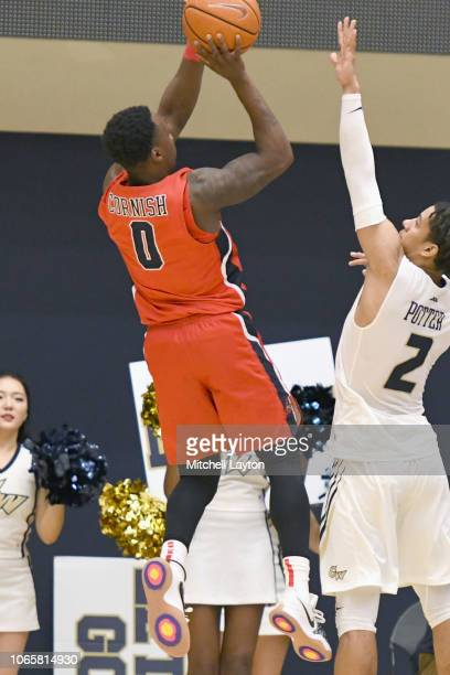 Jaron Cornish of the Stony Brook Seawolves takes a shot over Armel Potter of the George Washington Colonials during a college basketball game at the...