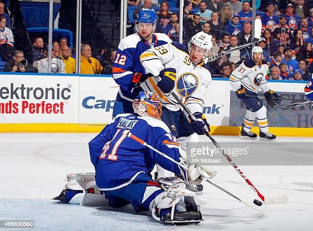 Jaroslav Halak and Josh Bailey of the New York Islanders defend the net against Tim Schaller of the Buffalo Sabres on April 4 2015 at Nassau Veterans...