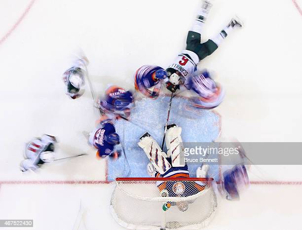 Jaroslav Halak and the New York Islanders defend against the Minnesota Wild at the Nassau Veterans Memorial Coliseum on March 24 2015 in Uniondale...