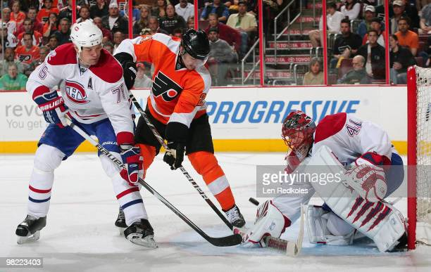 Jaroslav Halak of the Montreal Canadiens makes a save with Hal Gill and James van Riemsdyk of the Philadelphia Flyers waiting for a rebound on April...