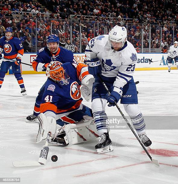 Jaroslav Halak of the New York Islanders comes out of the net to hit the puck away from Trevor Smith of the Toronto Maple Leafs during the third...