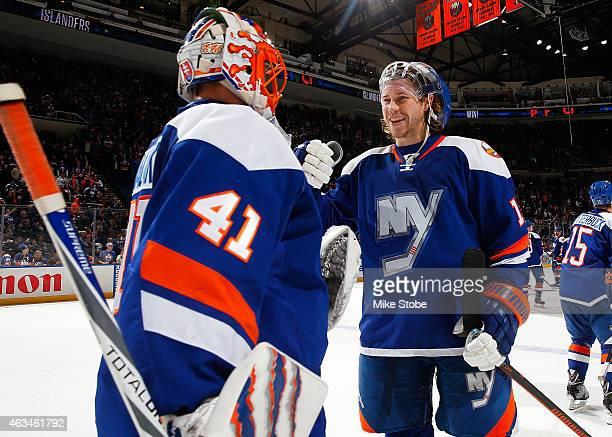 Jaroslav Halak of the New York Islanders is congratulated by teammate Matt Martin after defeating the Columbus Blue Jackets at Nassau Veterans...