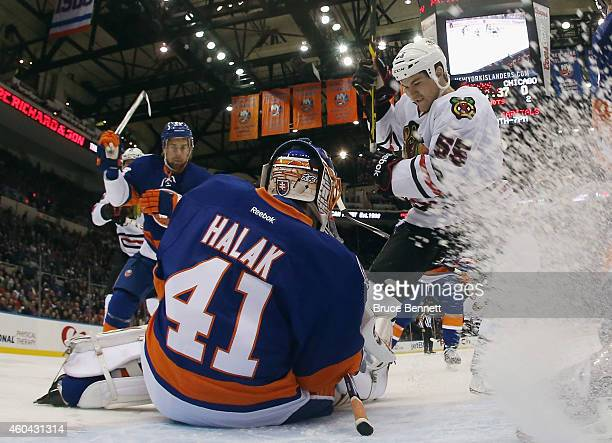 Jaroslav Halak of the New York Islanders makes the first period save as Andrew Shaw of the Chicago Blackhawks looks for the rebound at the Nassau...