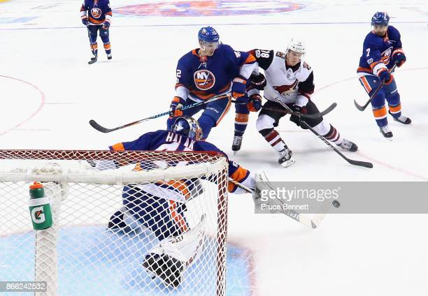 Jaroslav Halak of the New York Islanders sweeps the puck away from Christian Dvorak of the Arizona Coyotes at the Barclays Center on October 24 2017...