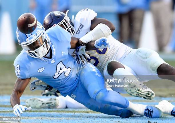 Jarquavius Wortham of the Western Carolina Catamounts forces a fumble by Rontavius Groves of the North Carolina Tar Heels during the first half of...