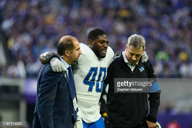 Jarrad Davis of the Detroit Lions is helped off the field after sustaining an injury in the first quarter of the game against the Minnesota Vikings...