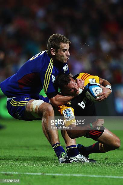 Jarrad Hoeata of the Highlanders tackles Aaron Cruden of the Chiefs during the round six Super Rugby match between the Chiefs and the Highlanders at...