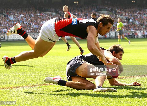Jarrad Waite of the Blues dives to gather the ball under pressure from Kyle Hardingham of the Bombers during the round four AFL match between the...
