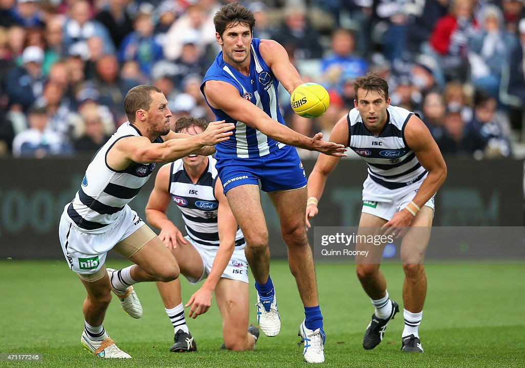 Jarrad Waite of the Kangaroos handballs whilst being tackled by James Kelly of the Cats during the round four AFL match between the Geelong Cats and the North Melbourne Kangaroos at Simonds Stadium on April 26, 2015 in Geelong, Australia.