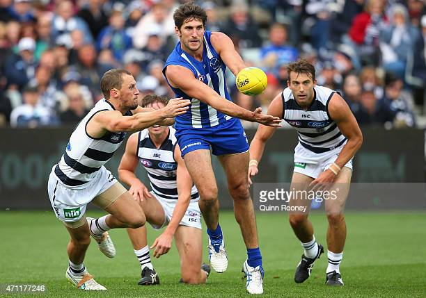 Jarrad Waite of the Kangaroos handballs whilst being tackled by James Kelly of the Cats during the round four AFL match between the Geelong Cats and...