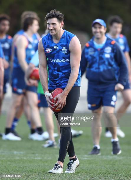 Jarrad Waite of the Kangaroos kicks the ball as Brad Scott coach of the Kangaroos looks on during an North Melbourne Kangaroos AFL training session...