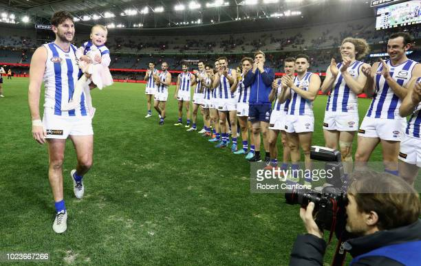 Jarrad Waite of the Kangaroos walks off the ground with his daughter Lola after playing his lass AFL match during the round 23 AFL match between the...