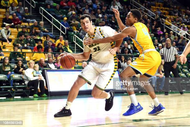 Jarred Reuter of the George Mason Patriots dribbles around Isaiah Rollins of the Southern University Jaguars during a college basketball game at the...