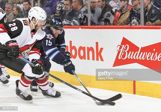 Jarred Tinordi of the Arizona Coyotes and Matt Halischuk of the Winnipeg Jets battle for the puck during first period action at the MTS Centre on...