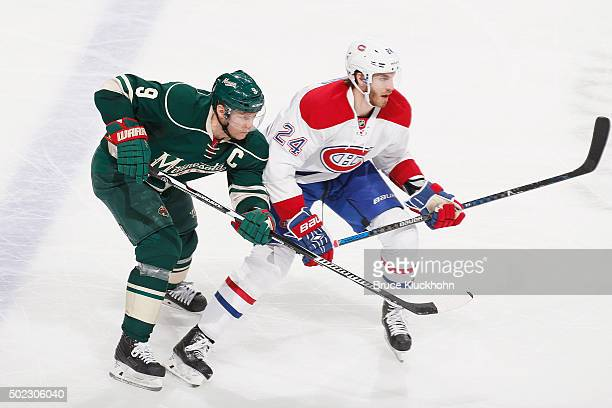 Jarred Tinordi of the Montreal Canadiens defends Mikko Koivu of the Minnesota Wild during the game on December 22 2015 at the Xcel Energy Center in...