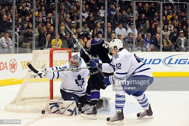 Jarret Stoll of the Los Angeles Kings battles for the puck against James Reimer and Tyler Bozak of the Toronto Maple Leafs at Staples Center on...