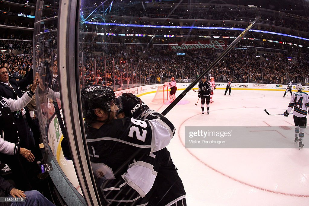 Jarret Stoll #28 of the Los Angeles Kings celebrates his goal with teammate Trevor Lewis #22 in the second period as Marc-Edouard Vlasic #44 of the San Jose Sharks skates away during the NHL game at Staples Center on March 16, 2013 in Los Angeles, California. The Kings defeated the Sharks 5-2.