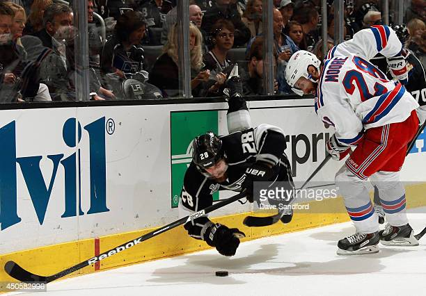 Jarret Stoll of the Los Angeles Kings dives for the puck in front of Dominic Moore of the New York Rangers in the second period of Game Five of the...