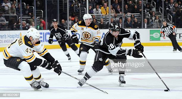 Jarret Stoll of the Los Angeles Kings handles the puck against Matt Bartkowski of the Boston Bruins at STAPLES Center on January 9 2014 in Los...