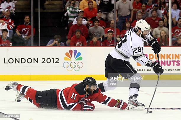 Jarret Stoll of the Los Angeles Kings handles the puck as Stephen Gionta of the New Jersey Devils hits the ice during Game Five of the 2012 NHL...