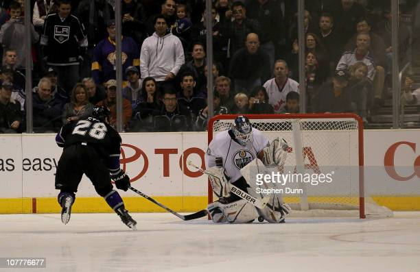 Jarret Stoll of the Los Angeles Kings shoots the puck under the pads of goaltender Devan Dubnyk of the Edmonton Oilers for what turned out to be the...