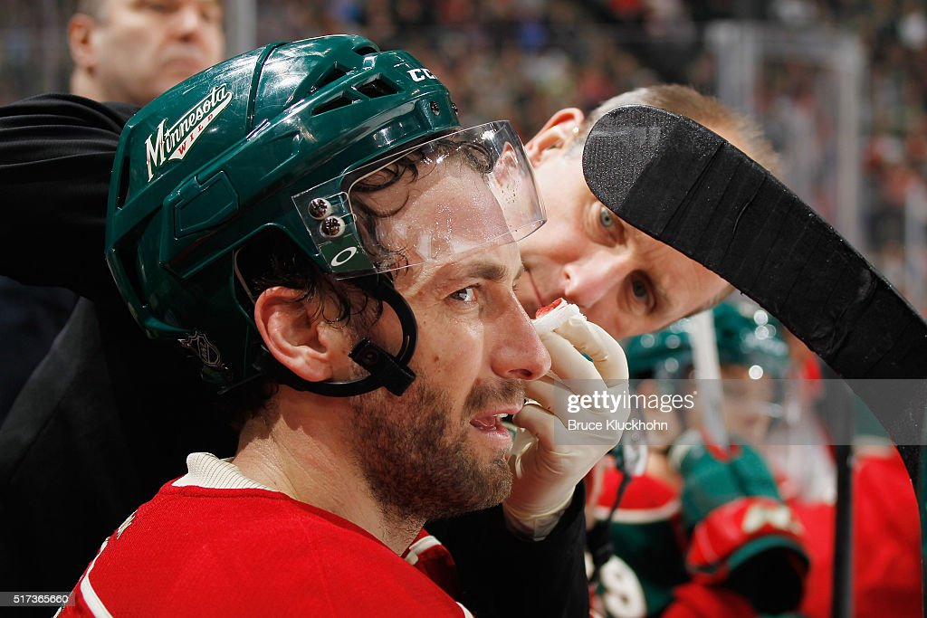 Jarret Stoll #19 of the Minnesota Wild is treated by a trainer during the game against the Calgary Flames March 24, 2016 at the Xcel Energy Center in St. Paul, Minnesota.