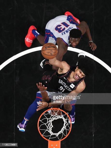 Jarrett Allen of the Brooklyn Nets battles for the ball against Langston Galloway and Khyri Thomas of the Detroit Pistons during their game at...