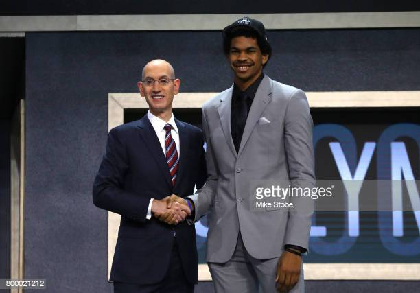 Jarrett Allen walks on stage with NBA commissioner Adam Silver after being drafted 22nd overall by the Brooklyn Nets during the first round of the...