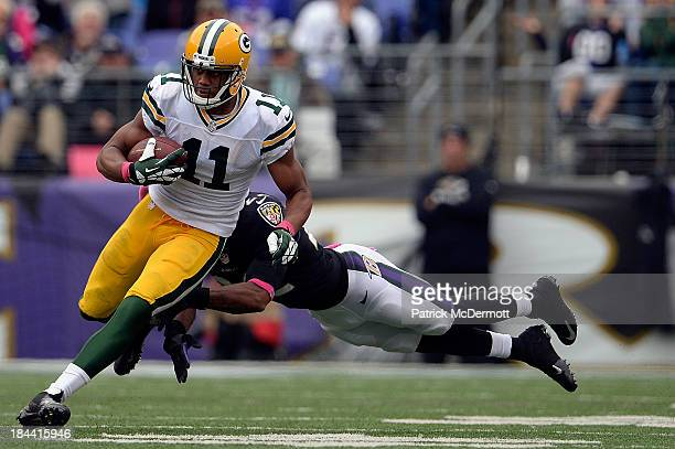 Jarrett Boykin of the Green Bay Packers avoids the tackle of Jimmy Smith of the Baltimore Ravens in the third quarter during a game at MT Bank...