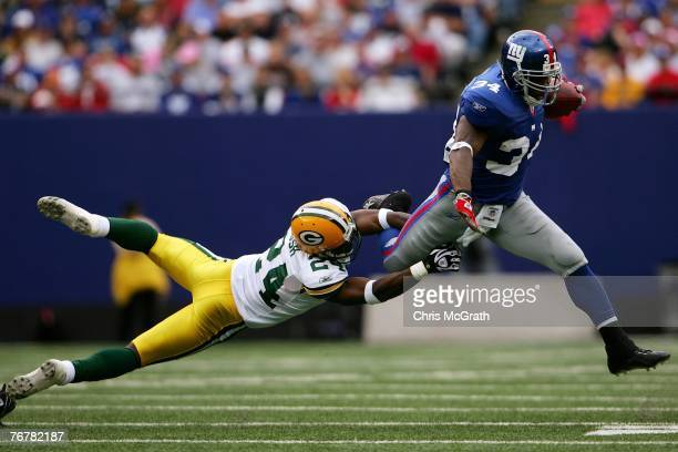 Jarrett Bush of the Green Bay packers dives to tackle Derrick Ward of the New York Giants on September 16 2007 at Giants Stadium in East Rutherford...